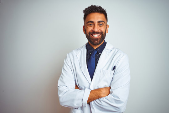 Young indian doctor man standing over isolated white background happy face smiling with crossed arms looking at the camera. Positive person.