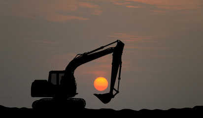 silhouette Excavator work on construction site at sunse