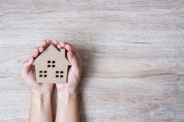 Hands holding house model on wood table background with copy space. Financial, money, refinance, Real estate and new home concept