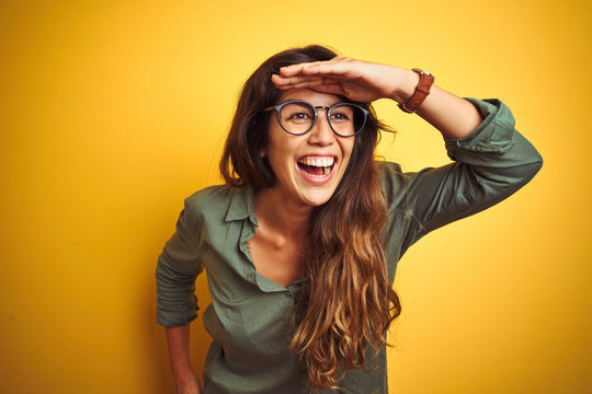 Young beautiful woman wearing green shirt and glasses over yelllow isolated background very happy and smiling looking far away with hand over head. Searching concept.