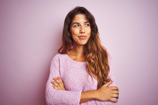 Young beautiful woman wearing sweater standing over pink isolated background smiling looking to the side and staring away thinking.