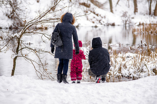 A couple with his son stands on the river Bank in winter