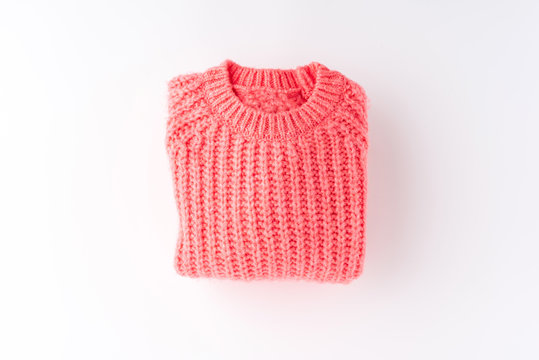 Pink folded sweater isolated on white background. Flat lay. Top view