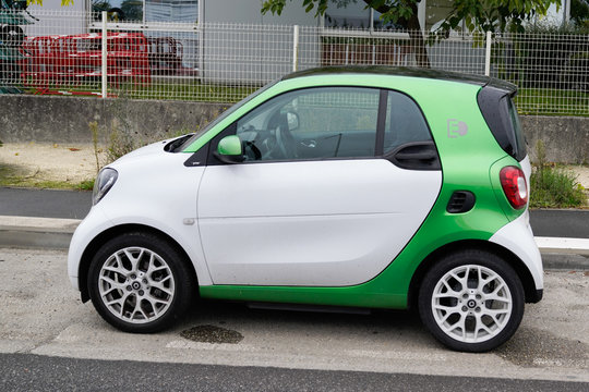 Electric Smart Car white and green parked street