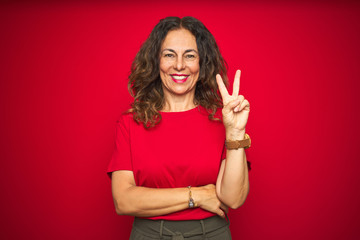 Wall Mural - Middle age senior woman with curly hair over red isolated background smiling with happy face winking at the camera doing victory sign. Number two.