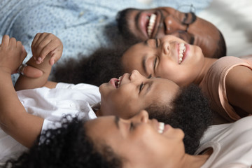 Close up of happy black family relax on bed together