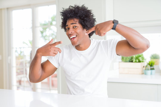 Young african american man wearing casual white t-shirt sitting at home smiling cheerful showing and pointing with fingers teeth and mouth. Dental health concept.