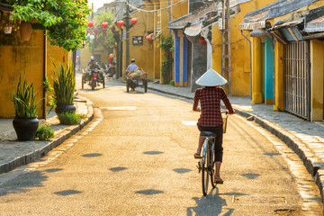 Vietnamese woman in traditional hat bicycling along Hoi An