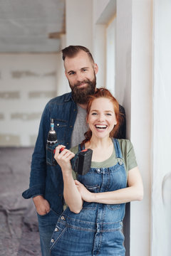 Man standing behind partner while she holds drill