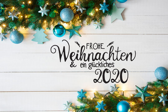 Turqouise Christmas Decoration With German Calligraphy Frohe Weihnachten Und Ein Glueckliches 2020 Mean Merry Christmas And A Happy 2020. Fir Tree Branch Border With Shiny Fairy Lights