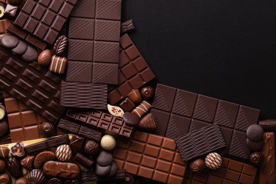 dark chocolate background, sweet bar and candy with empty space for text
