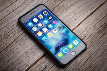UZHGOROD, UKRAINE - DECEMBER 15, 2016: New black iPhone 7 Plus from the company Apple on a woden background, studio photo, on December 15, 2016 in Uzhgorod, Ukraine.