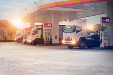 Trucks refueling in petrol station, Transportation vehicle, Business logistics, delivery transport, cargo logistic concept. Freight shipping, at sunset background.