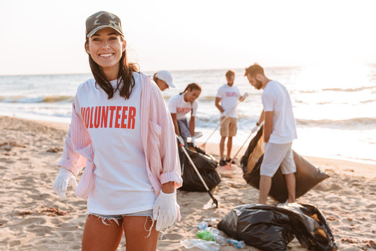 Smiling young girl volunteer cleaning beach from garbage