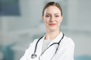 smiling female family doctor in doctor's overall with stethoscope in front of a clinic room