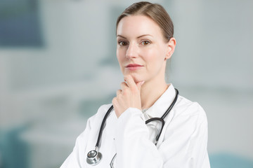 thinking female family doctor in doctor's overall with stethoscope in front of a clinic room