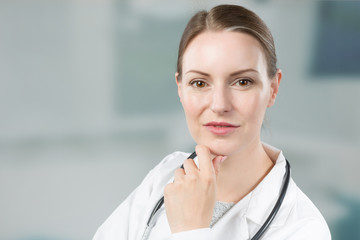 portrait of thinking female family doctor in doctor's overall with stethoscope in front of a clinic room