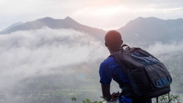 African man hiker with backpack at the top of the hill covered with mist.16:9 style