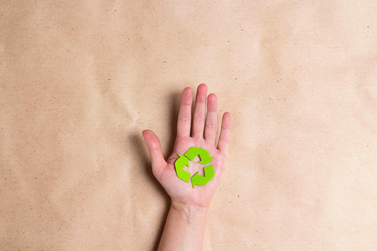 Female hands hold a recycles eco symbol on brown paper background.