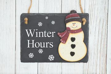 Winter Hours hanging chalkboard sign with a snowman