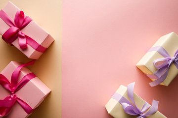 top view of gift boxes with ribbons on pink and beige background