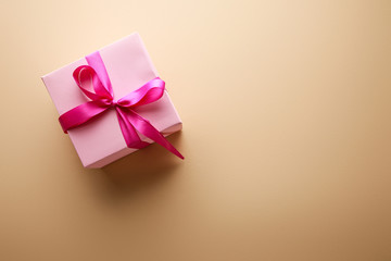 top view of pink gift box with ribbon on beige background
