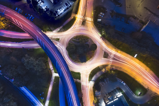 Transportation at night with commuting vehicle traffic creating light trails on the road with motion blur, roundabout and motorway interchange in city, drone aerial photography with long exposure