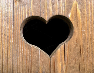Herzausschnitt aus Holz in Toilettenhäuschen in den Alpen