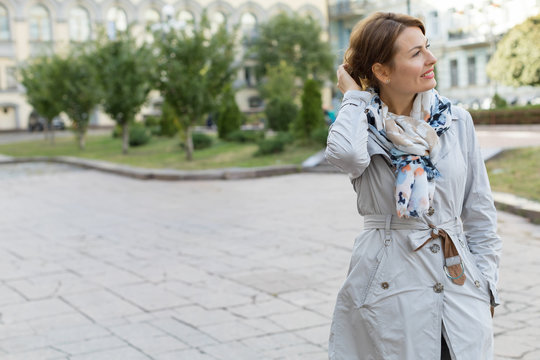 Portrait of a happy smiling adult woman over city background. Place for text.