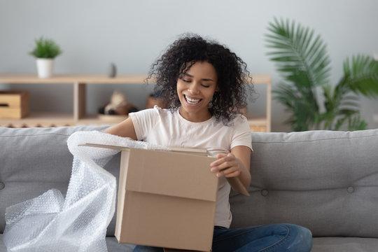 Smiling black girl unpack parcel at home shopping online