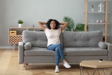 Fotorollo Entspannung Happy black girl relaxing on cozy sofa at home
