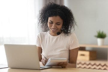 Smiling biracial woman make notes studying on laptop at home