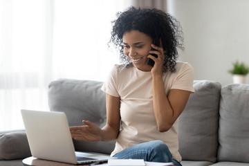 Smiling black woman multitask at home using gadgets