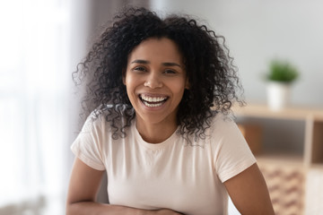 Portrait of smiling black millennial girl posing at home