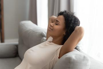 Fototapeta Calm black young woman relax on sofa hands over head obraz