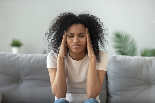 Exhausted black woman massage head suffering from migraine