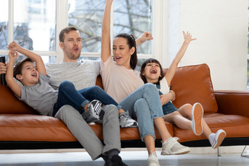 Overjoyed family of four watching football basketball match on tv.