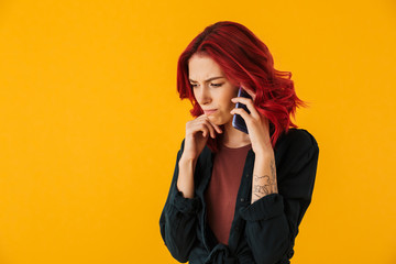 Image of young perplexed woman talking on cellphone