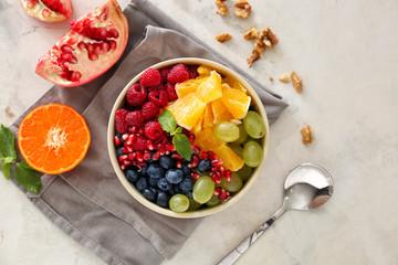 Fotobehang - Bowl with tasty fruit salad on light background