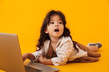 Image of amazed nice girl typing on laptop while lying on floor