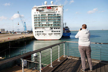 A man takes a picture of Ventura cruise ship in the port of Zeebrugge