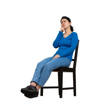 Side view full length portrait of casual young woman seated on a chair keeps hand under chin thoughtful looking away isolated over white background with copy space.