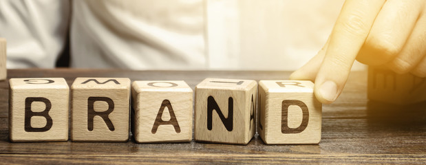 Businessman puts wooden blocks with the word Brand. Business, marketing, and advertising. Name, term, design, symbol that identifies one seller's good or service.