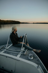 young man in a boat at sunset