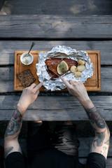 Tattooed man eating salmon