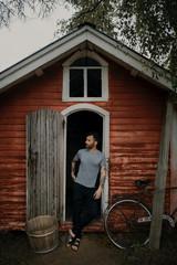 man in front of old door of a cabin