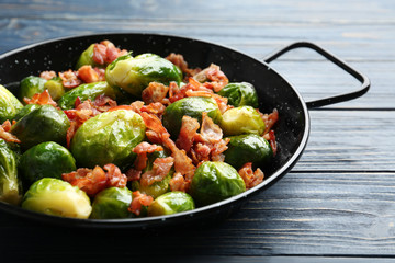 Tasty roasted Brussels sprouts with bacon on blue wooden table, closeup