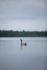 man fishing on a boat in a lake