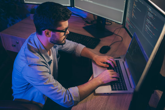 Profile photo of it specialist guy working late at night sitting comfy office chair holding hands on keyboard looking monitors website debugging expert dark office indoors