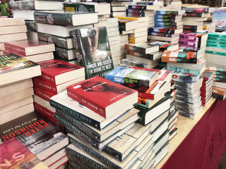 KUALA LUMPUR, MALAYSIA -JULY 07, 2019: Books on the table for sale in the huge warehouse. All books are grouped and segregated by title and genre to facilitate customers.